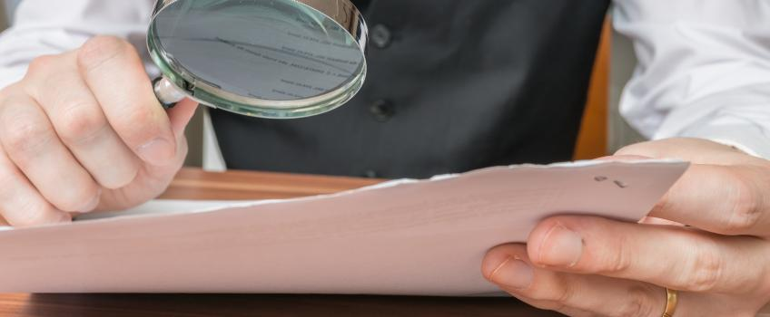 Man looking at a report through a magnifying flass