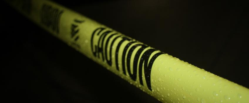 "Yellow police tape with black writing saying ""caution"", against black background"