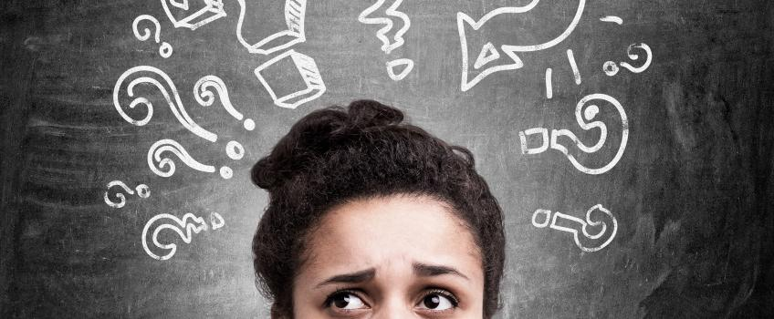 Woman's face looking confused against blackboard with question marks drawn onto it