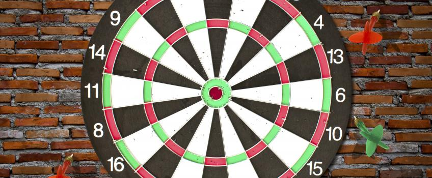 Dartboard against brick wall with darts missing target