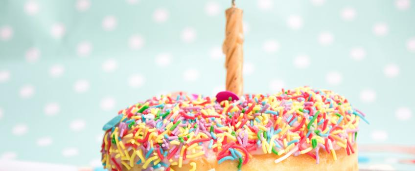 Doughnut covered in sprinkles with candle on top against green background