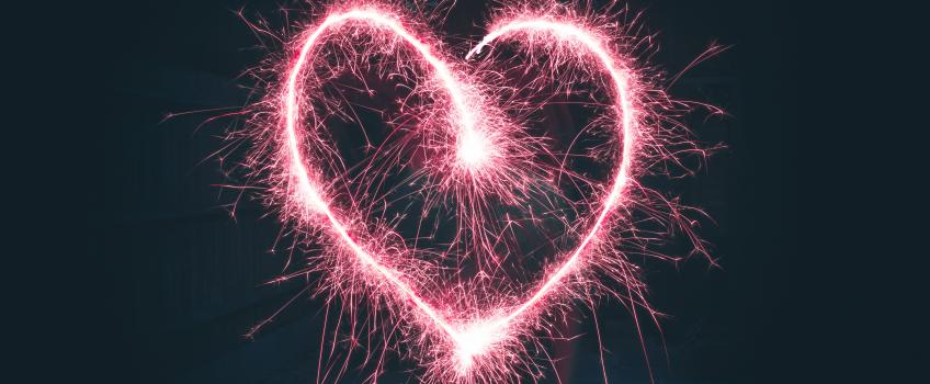 Red firework heart lit up against black sky