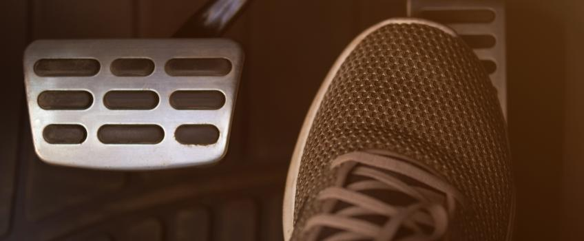 Person's foot on an accelerator pedal.