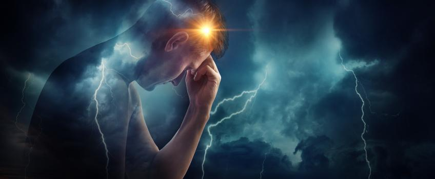 Man holding head against dark background with clouds and thunder