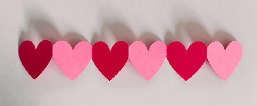 Chain of pink and red hearts cut out of paper