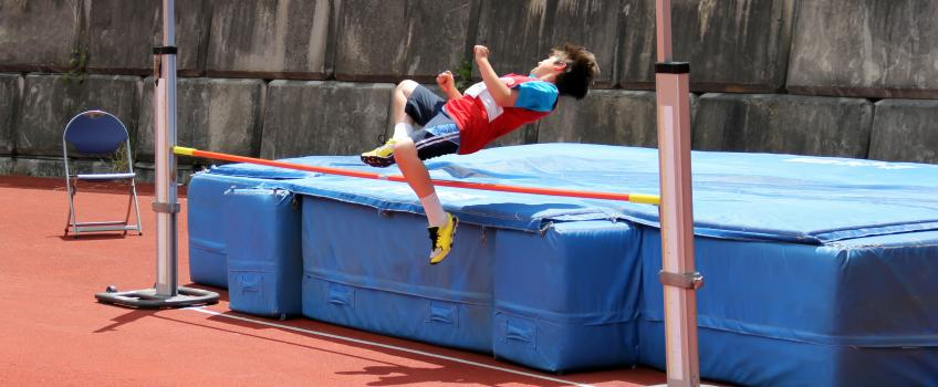 Child jumping high jump with low bar
