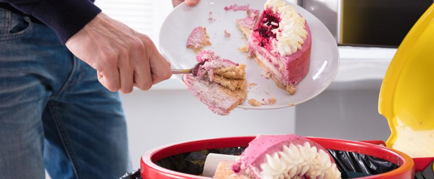 Close up of man scraping plate of pink and white cake into the bin