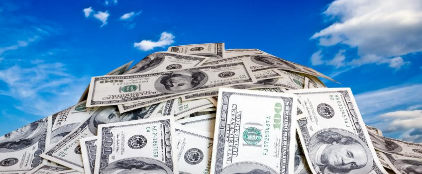 Pile of US dollars against blue sky