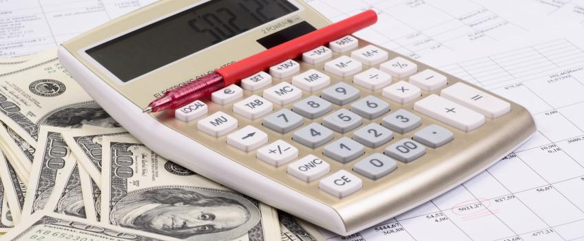 Calculator with pen and dollars.