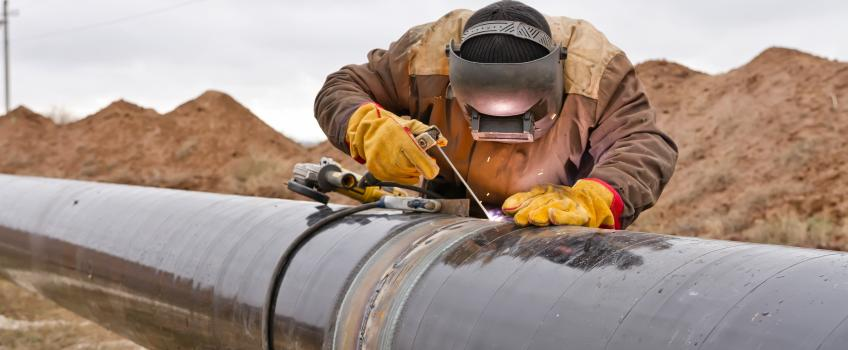 Workman welding a gas pipeline