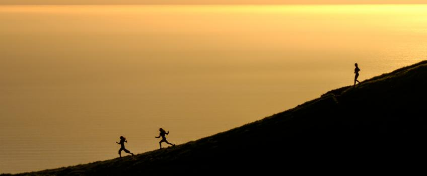 Silhouettes of three people running downhill against golden background