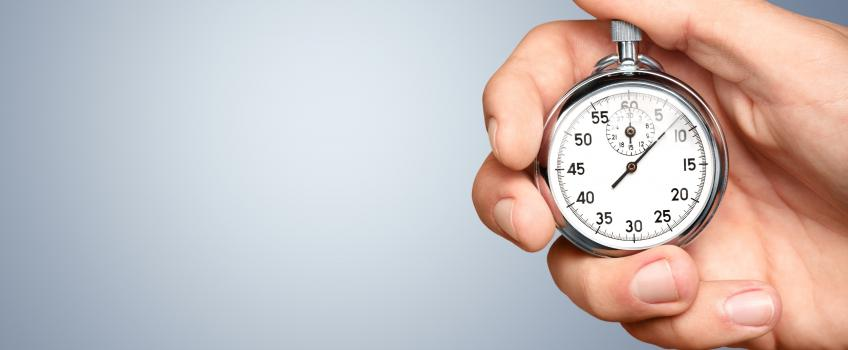 Hand holding old-fashioned stopwatch against grey background