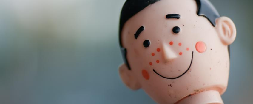 Acne spots on the face of a vintage toy doll head