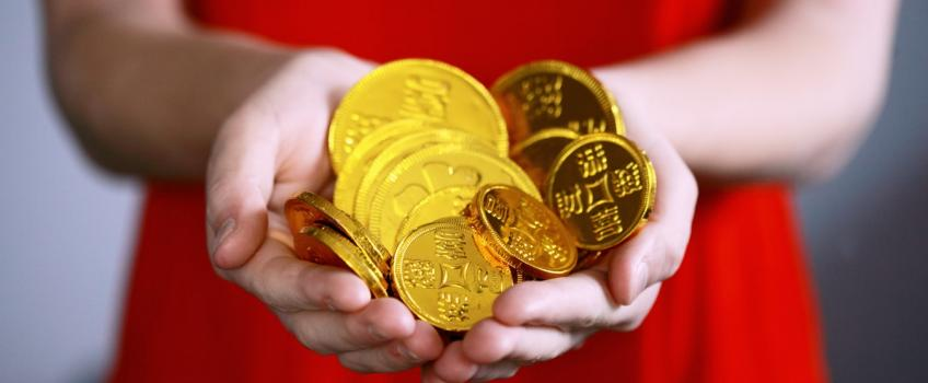 Person holding gold-covered chocolate coins
