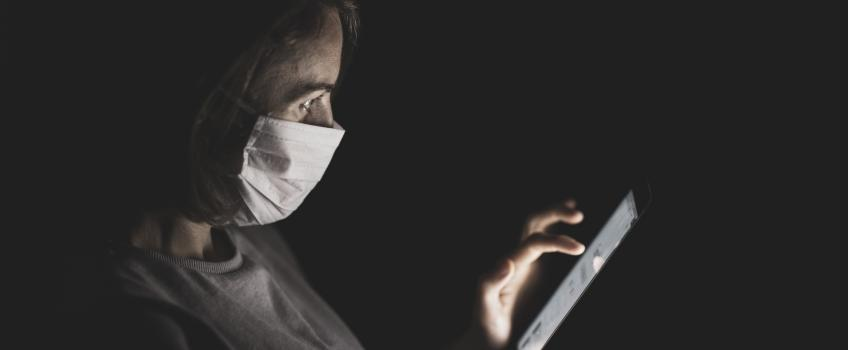 Doctor in face mask tapping on a computer screen.