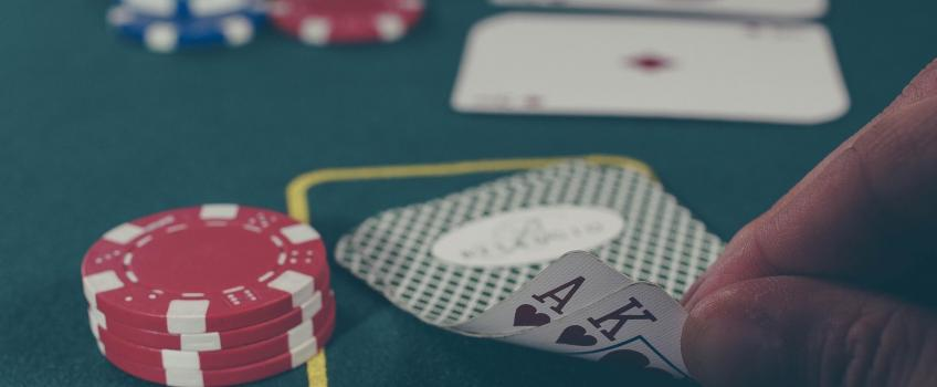 Hand turning over cards during game of blackjack in casino, next to pile of red chips
