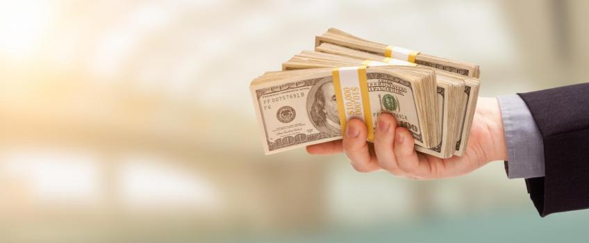 Man's hand holding wads of $100 bills