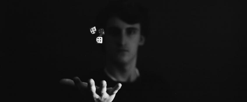 Man throwing three dice into the air.