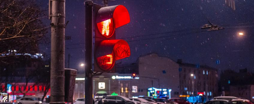 Red traffic light against snow background